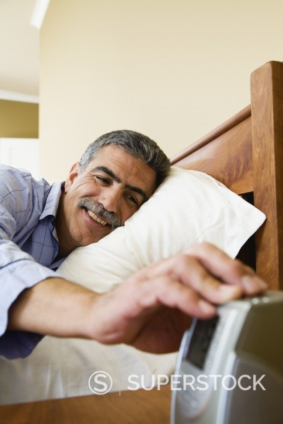 Stock Photo: 1589R-91486 Middle-aged Hispanic man turning off alarm clock