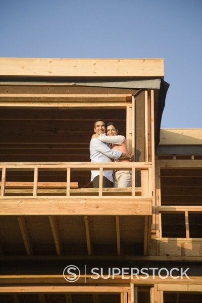 Stock Photo: 1589R-98586 Hispanic couple hugging on balcony at construction site