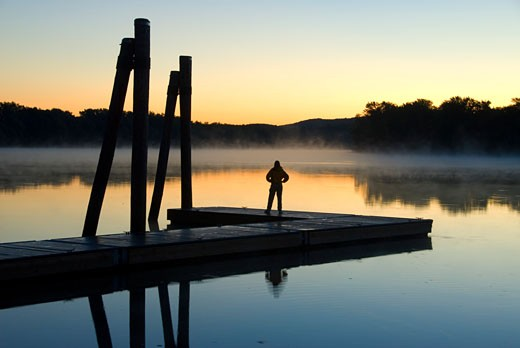 Stock Photo: 1596-1198A Silhouette of a person standing on a pier at dawn, Connecticut River, Ferry Park, Rocky Hill, Connecticut, USA