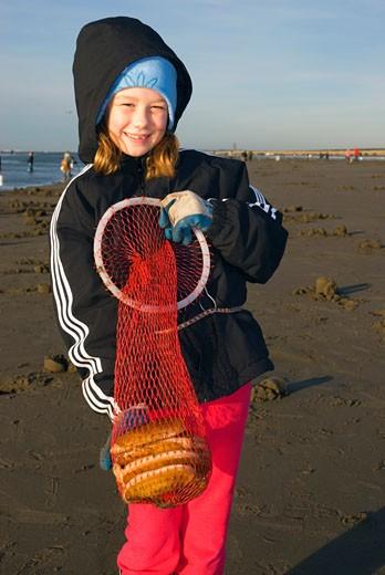 Stock Photo: 1596-1329 Girl holding razor clams in a fishing net, Long Beach, Washington State, USA