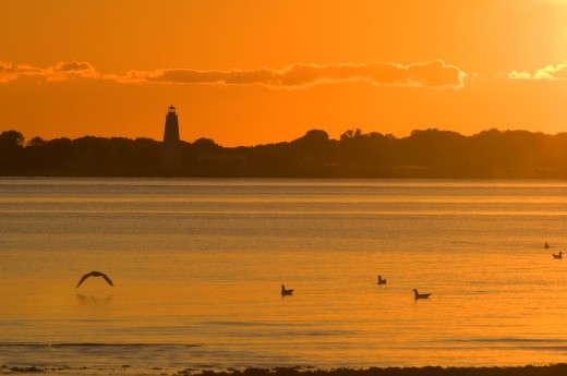 River at sunset with a lighthouse in the background, Lynde Point Lighthouse, Connecticut River, Long Island Sound, Griswold Point Preserve, Connecticut, USA : Stock Photo
