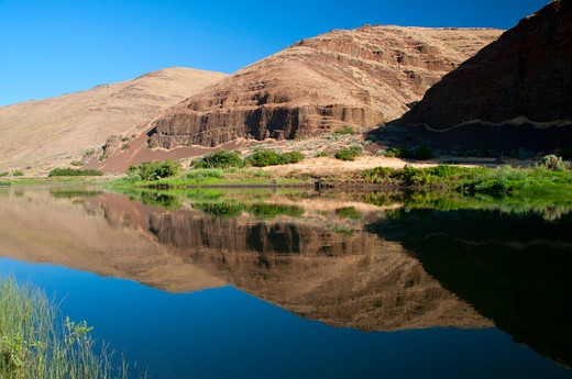 Reflection of hills in water, John Day River, John Day River State Scenic Waterway, Murtha Ranch, Oregon, USA : Stock Photo