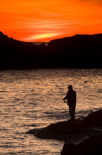 Silhouette of a fisherman fishing, Cape Neddick Light Station, Sohier Park, York Beach, York, York County, Maine, USA : Stock Photo