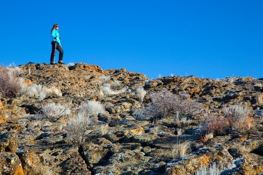 USA, Oregon, Christmas Valley National Back Country Byway, Fort Rock State Park, Woman standing atop and looking over Fort Rock outcrop : Stock Photo