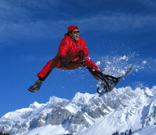 Stock Photo: 1597-109480  winter sports, sport, mountain range, man, red ski suit, ski, Snowscooter, fun, joke, jump, variations, variants,