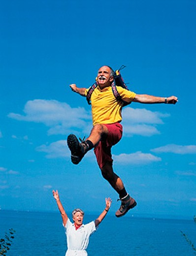 Stock Photo: 1597-12298 aerial jump, backpack, cheering, coast, couple, hiking, joy, jump, lake, middle age, nature, old person, outside, se