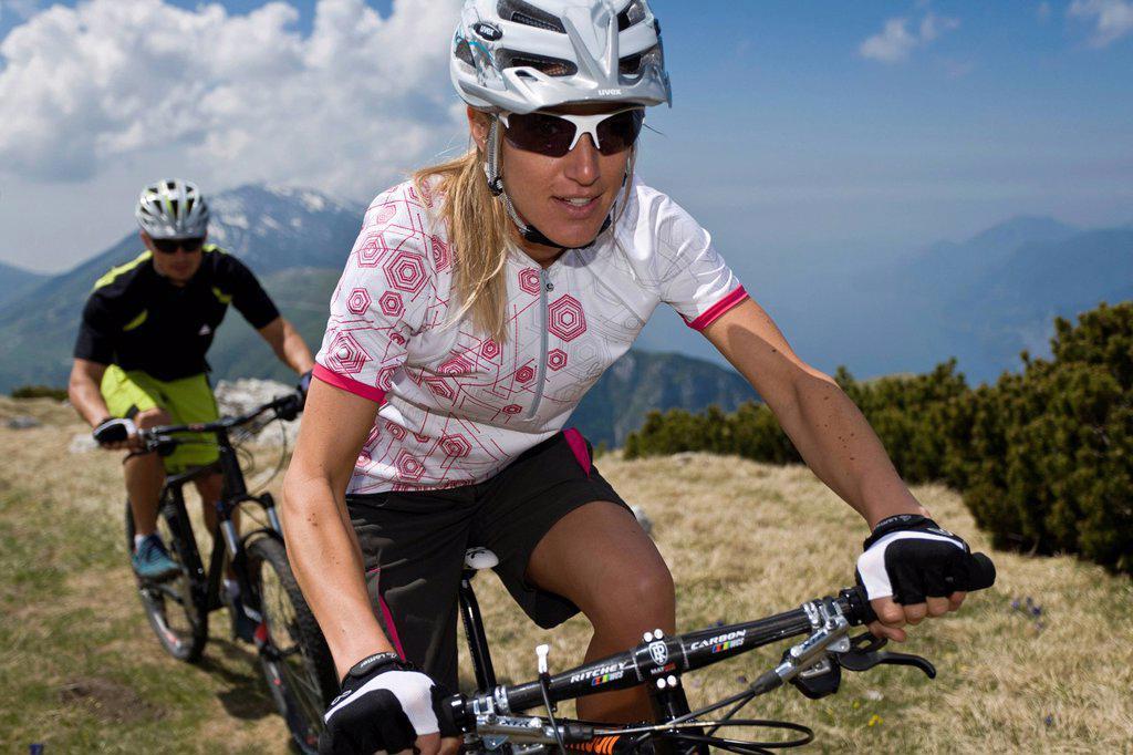Mountainbiking, woman, mountains, bike, man, go, biking, sport, extreme sport, blue, sky, action, Monte Baldo, lake Garda, South Tirol, Italy, : Stock Photo