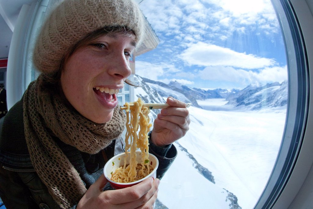 Stock Photo: 1597-167786 Mountain, mountains, glaciers, ice, moraine, canton Bern, Valais, Wallis, Switzerland, Europe, food, eating, Bernese Oberland, Jungfrau, Alps, woman, noodle soup, Korean, snow, window, Jungfraujoch, Aletsch glacier, Switzerland, Europe,