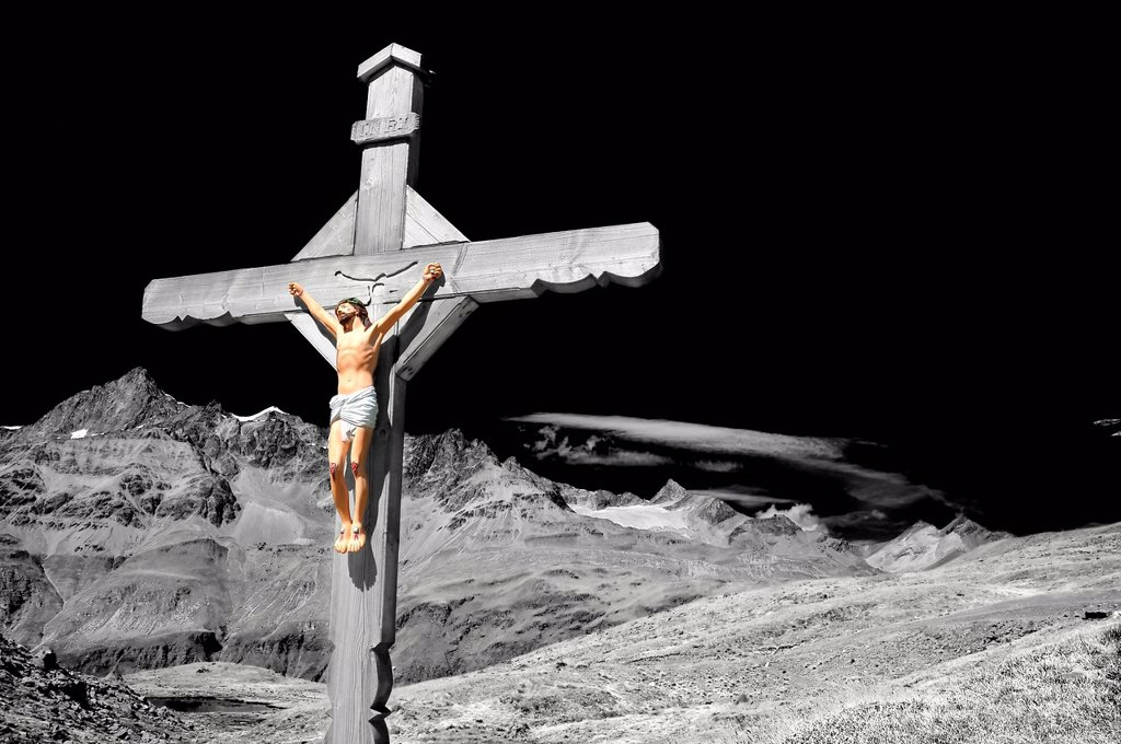 Stock Photo: 1597-175024 Stunning and dramatic enhanced monochrome cross with jesus christ crucified, in the mountains, above a lake, with high alps in the distance,