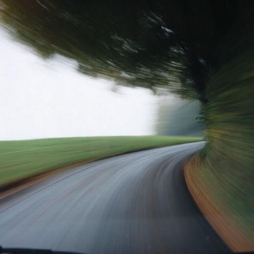 Stock Photo: 1597-4096  field, curve, country road, street, blurs, distorts, edge of forest, fast