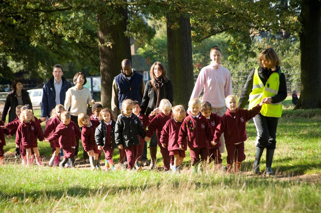 Junior school children, supervised walk, teachers, school, uniform, educate, children, child, junior, young, teacher, supervisor, supervise, care, walk, street, park, hold_hands, line, pairs, cross_road, high, visibility, jacket, waist, coat, crocodile_li : Stock Photo