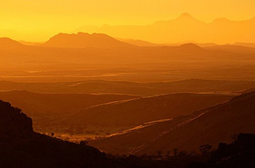 Sunset, at Mowani Mountain Lodge, Damaraland, Kunene Region, Namibia, Africa, twilight, yellow, silhouettes, landscape, scenic, scenery, mountains, dusk, misty, mist, haze, hazy : Stock Photo