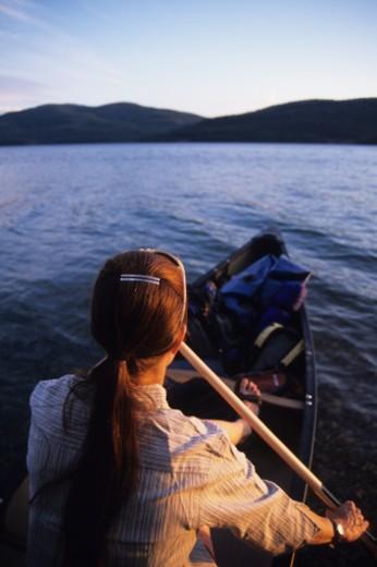 Solo female padding loaded canoe across lake at sunset. : Stock Photo