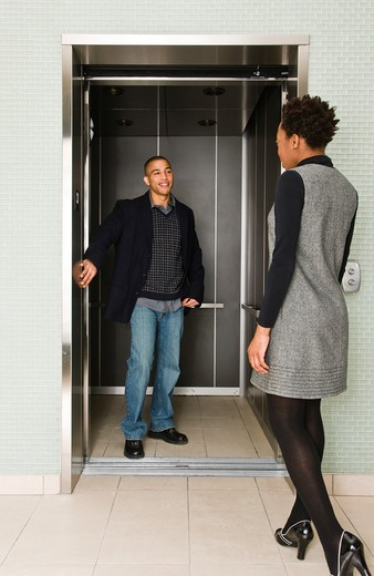 Man holding door for woman : Stock Photo