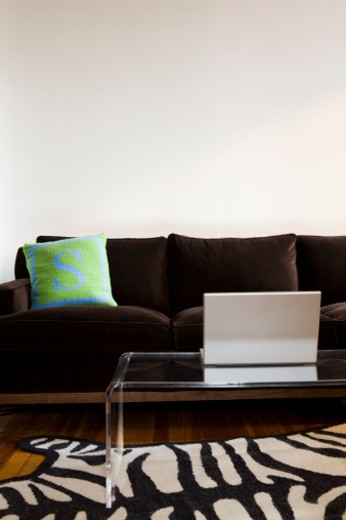 Laptop on coffee table in living room with couch : Stock Photo