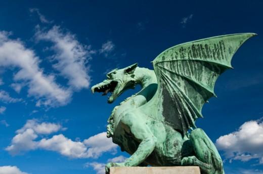 One of the four bronze dragons on the Dragon Bridge spaning the river Ljubljanica in Ljubljana : Stock Photo