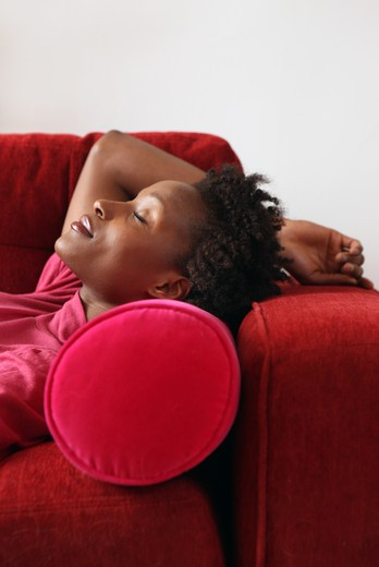Stock Photo: 1598R-10002641 Woman lying on a pink couch with her head on pink pillow, her arm behind her head.