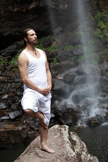 Man doing yoga in a rainforest : Stock Photo