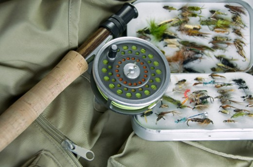A fly fishing rod, reel, and box of dry flies resting upon a fishing vest. : Stock Photo