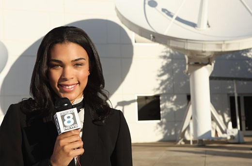 Female reporter  standing outside near large satellite dishes, reporting the news. : Stock Photo