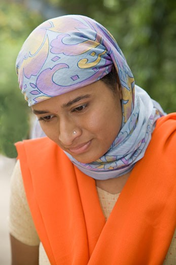 Young Indian Muslim woman wearing multicolored hijab or head scarf looking down. : Stock Photo