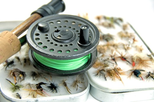 A flyfishing rod and reel resting upon a box of flies. : Stock Photo