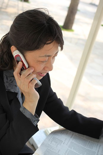 Stock Photo: 1598R-10005086 Chinese businesswoman talking on cell phone and reading newspaper.