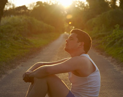 Young runner resting on country lane. : Stock Photo