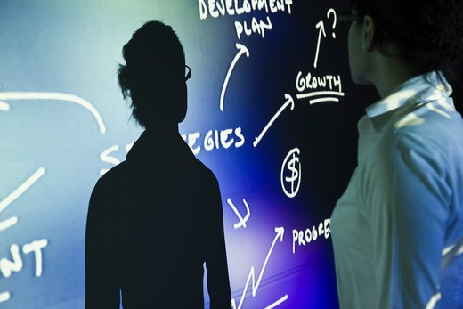 Shadow and businesswoman in front of business plan projection : Stock Photo