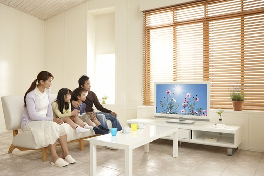 A family watching TV in the living room. : Stock Photo