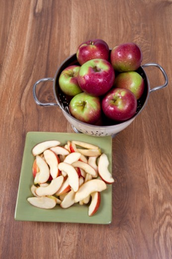 MacIntosh apples in a colander and apple slices. : Stock Photo