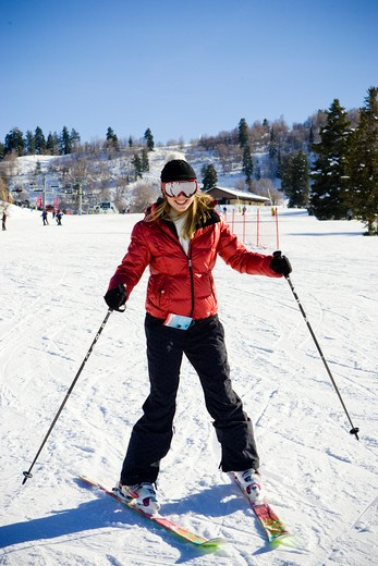 Young woman in ski parka smiling while skiing beginner run. : Stock Photo