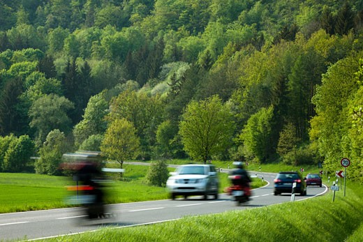 cars and motorbikes driving on a country road in a valley, motion blur, Franconian Switzerland (Fraenkische Schweiz), Bavaria, Germany : Stock Photo