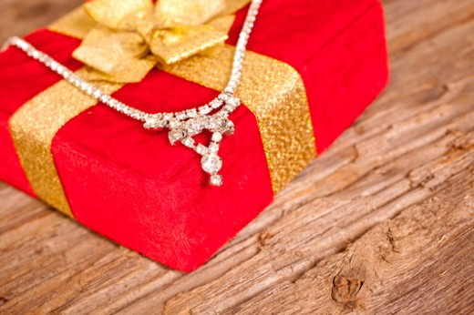Red gift box with diamond necklace on rough weathered boards : Stock Photo