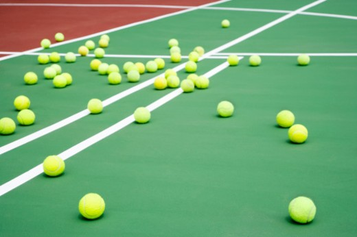 tennis court littered with tennis balls : Stock Photo