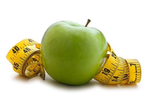 An apple in front of a coiled up tape measure. : Stock Photo