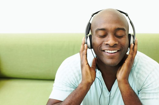 Stock Photo: 1598R-10008874 Young man wearing headphones, smiling with eyes closed