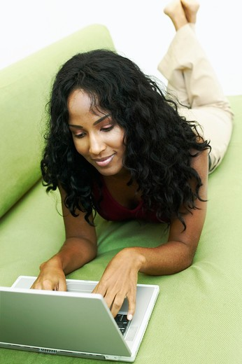 Young woman lying on green sofa, using laptop : Stock Photo