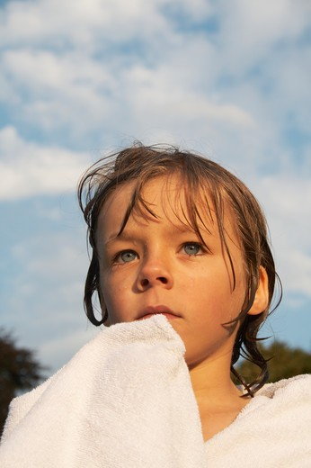 Boy (6-7) wrapped in towel with wet hair outdoors : Stock Photo
