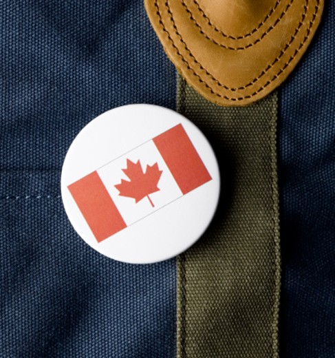 Canadian flag button on bag, close-up : Stock Photo