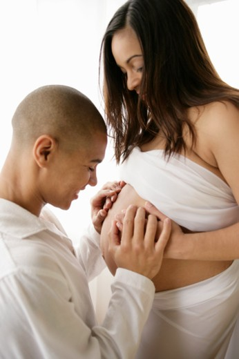 Man touching pregnant woman's belly, side view, studio shot : Stock Photo