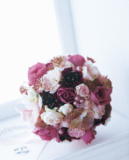 Round bouquet of rose, spray rose, scabiosa, astrantia and tulip by window : Stock Photo