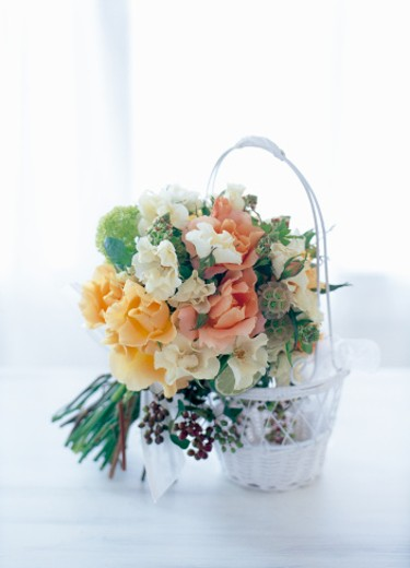 Spray rose, viburnum, scabiosa, italian berry, reseda, lime and sweet william arranged in white basket : Stock Photo