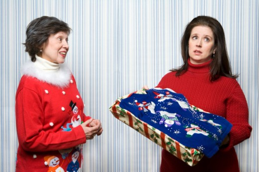 Mature daugther receiving Christmas sweater gift from mother, studio shot : Stock Photo