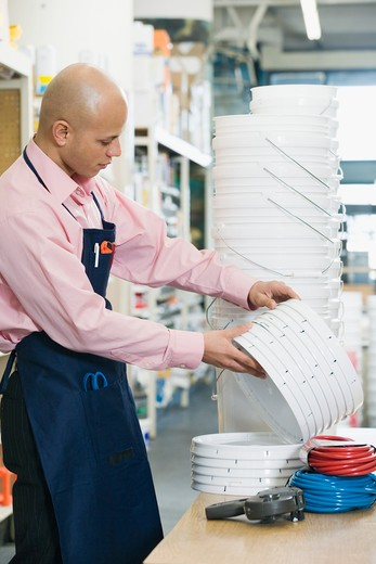 Sales clerk holding bucket coveres behind counter : Stock Photo