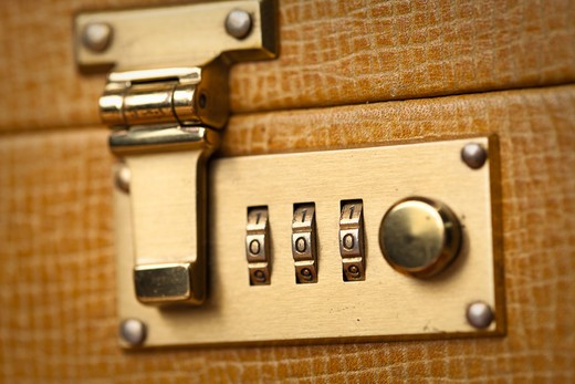 Close up of a gold toned briefcase lock : Stock Photo