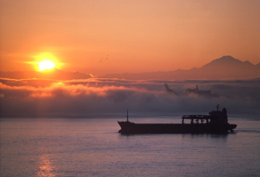 Stock Photo: 1598R-10012699 Freighter ship leaves port at sunrise