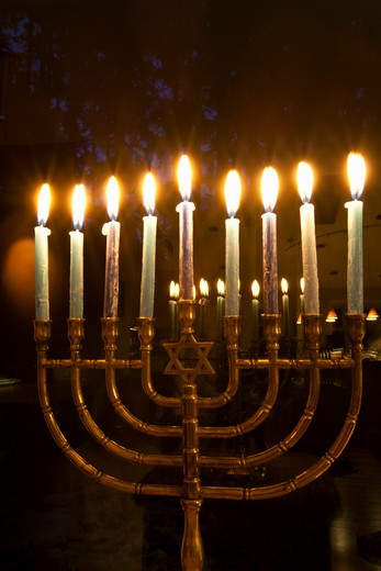 Lit candles in a menorah in evening light, commonly used during the Jewish celebration of Hanukkah. : Stock Photo