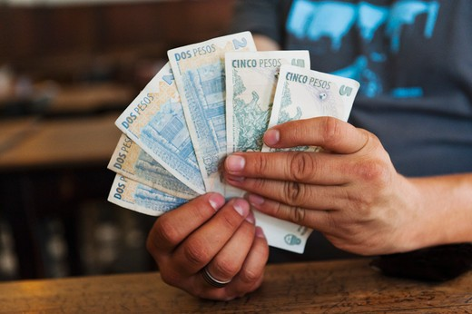 Argentina, Buenos Aires, Man holding Argentinian peso notes : Stock Photo