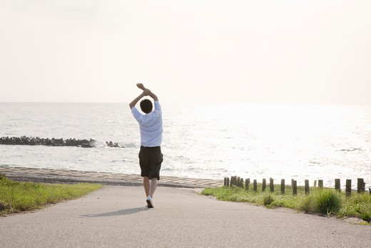 man walking and stretching out at seaside : Stock Photo